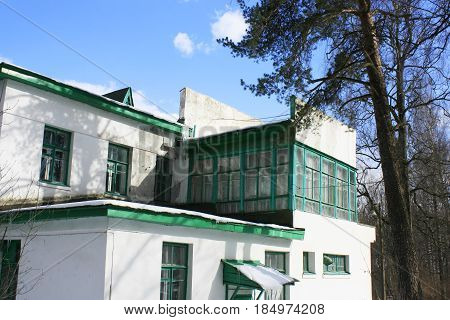 Old house of 40-es in the village of Pavlovo Leningrad Region Russia.Side view two-story white brick building with green windows and visors ice on the roof and visor at the entrance. Near large pine. Clear sunny winter day.