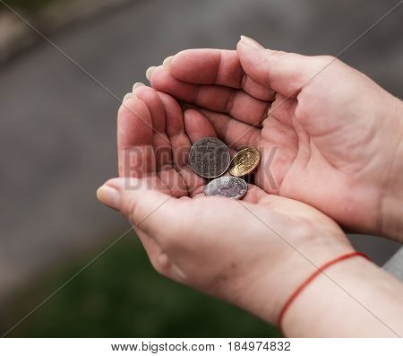 Hands of senior woman with coins closeup. Poverty concept