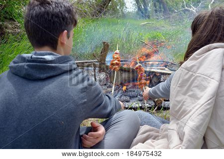 Teenagers enjoying together barbecue outdoors, close up