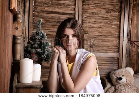 A young woman in white sits in a country house in anticipation of Christmas.