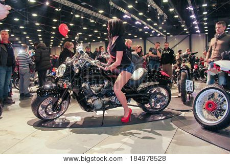 St. Petersburg Russia - 15 April, A fashion model on a motorcycle among visitors,15 April, 2017. International Motor Show IMIS-2017 in Expoforurum. Models on motorcycles presented at the motor show.