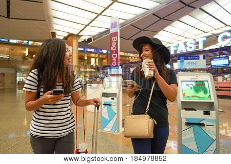 SINGAPORE - CIRCA AUGUST, 2016: young women at Singapore Changi Airport Terminal 2 departure hall