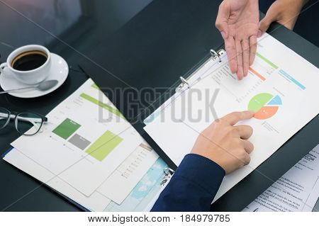 Hand point at a report with command command concept of business soft focus and vintage tone.
