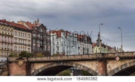 PRAGUE CZECH REPUBLIC - NOVEMBER 4 2012: The fragment of Palacký bridge and houses on the embankment of Prague. View from the river boat. Walking on a river boat on the Vltava River are popular among tourists