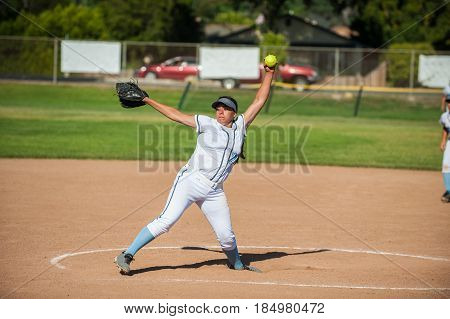 White uniform fast pitch softball pitcher winding up to throw in side view.