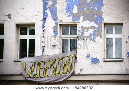 A sheet with slogan hangs in front of an occupied apartment in front of an old building in Berlin Kreuzberg.