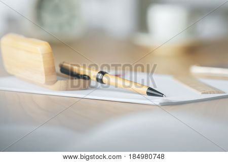 Close up of brown pen with wooden case on table with blurry clock and coffee cup