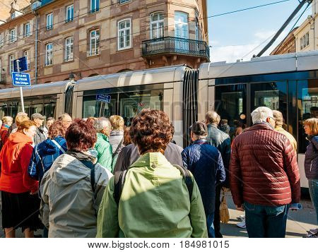 STRASBOURG FRANCE - APR 27 2017: Group of senios tourists waiting for hte tramway to pass to discover the French city of Strasbourg Alsace