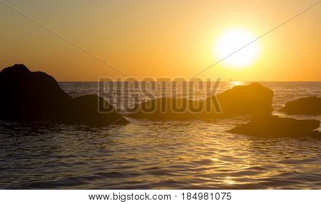 Sunrise over the sea with stones. Pacification and happyness concept. Beautiful nature landscape