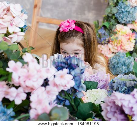 Lovely cute little girl hid her face behind a bouquet of artificial colorful flowers. Grey wall and the stairs on the background. Daughter hides from her mom