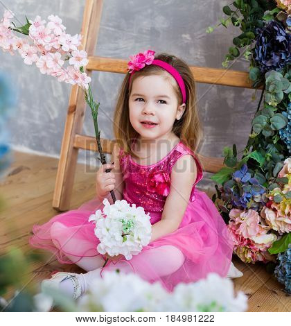 Smilling little girl in beautiful pink dress is sitting near the wooden stairs and colorful flowers. Cute girl is holding flower in her hands