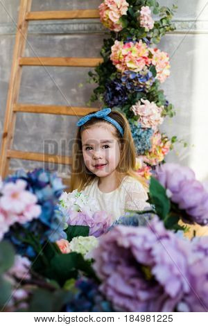 Beautiful little girl posing with a large bouquet of lilac flowers in a white lacy dress at home. Wooden stairs decorated with colorful flowers on the background