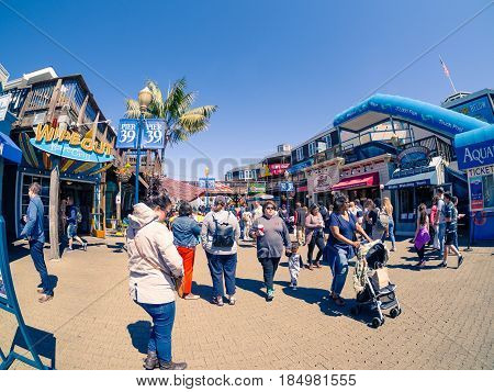 San Francisco, CA, USA - April 3, 2017: Crowds of tourists, mainly families,  walking near the entrance of Pier 39, Fisherman's Wharf