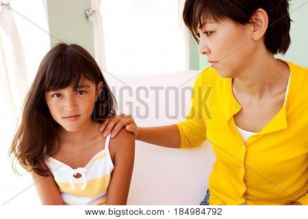 Caring mother talking and consoling her daughter