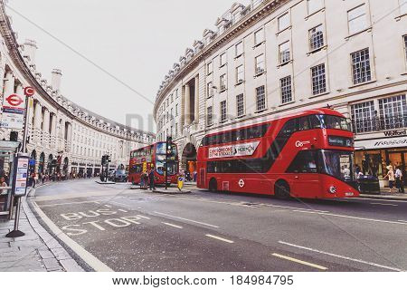 LONDON UNITED KINGDOM - August 09 2015: Architecture in London's Regent Street a very central shopping and luxury location featuring the characteristic red double decker buses