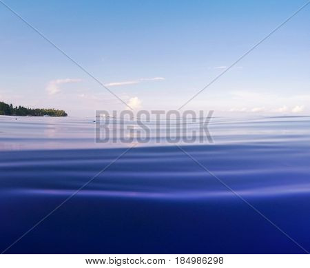 Bright blue sea with ripples and distant shore. Double landscape with sea water and sky. Tropical seaside photo. Above and below waterline. Natural scene with ocean water surface. Still sea by beach