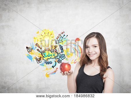 Portrait of a smiling young woman with brown hair wearing a black tank top and holding a red apple standing near a concrete wall with a nutrition idea sketch on it.