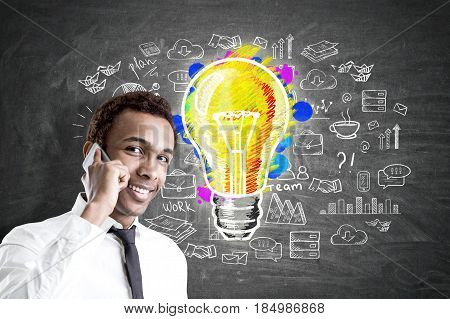 Portrait of a young smiling African American businessman with a smartphone standing near a blackboard with a colorful light bulb and business sketch on it.