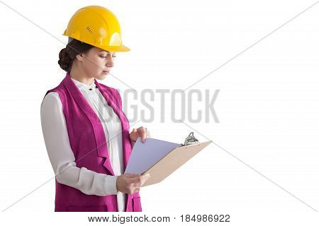 Isolated portrait of a woman wearing a yellow hardhat and a pink west and holding a clipboard with documents.