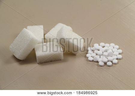 Heap of sweetener tablets and five sugar cubes