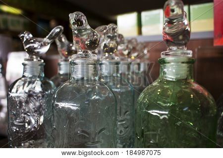 Dumaguete Philippines - 26 November 2016: Glass ware home decor in shopping mall. Wine bottles with glass birds. Fancy glassware in shop. Shiny house decor. Selling dining ware. Kitchen ware on sale
