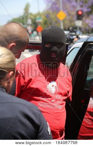 LOS ANGELES California- May 1, 2017: A person in a Black Ski Mask is arrested and put in a police car at a Protest Rally Against President Donald J.Trump on May 1, 2017 in Los Angeles, California