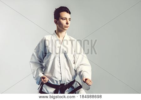 Girl In Karate Suit Kimono In Studio At Grey Background. Female Child Shows Judo Or Karate Stans In