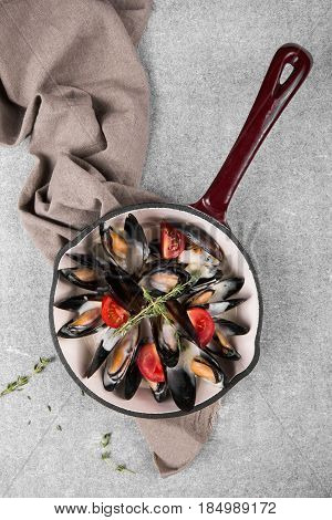 Cooked mussels in a pan served on a napkin garnished with tomatoes and thyme. Steamed mussels in white wine sauce. Seafood mussels on pan with cream sauce. Top view.