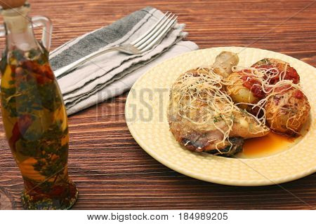 Roasted chicken legs with potato on wooden background