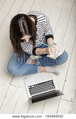 Beautiful young happy woman working with a laptop and conducts recording in a notebook sitting on a white wooden floor