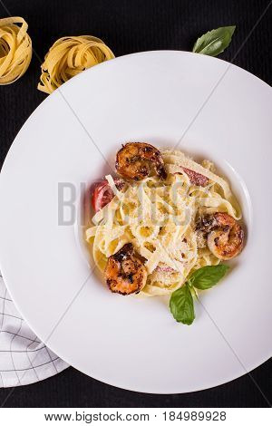Seafood. Shellfish. Pasta with grilled prawns shrimps, with tomatoes, fresh herbs basil and spices. On a black cast-iron frying pan on a black concrete table, Top view, copy space