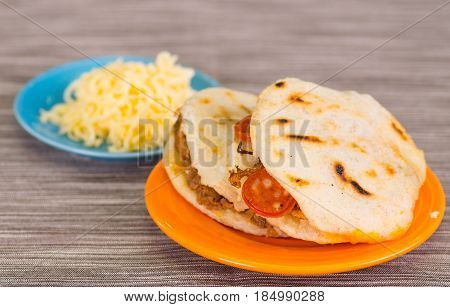 Traditional delicious arepas, shredded chicken avocado and cheddar cheese and shredded beef with grated cheese on wooden background.