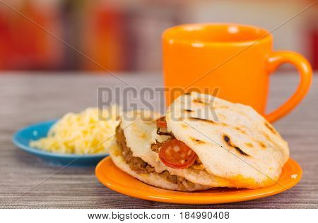 Traditional delicious arepas, shredded chicken avocado and cheddar cheese and shredded beef with a orange cup on wooden blackground.