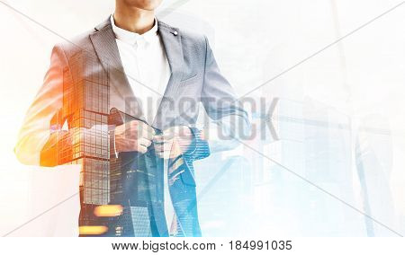 Close up of an unrecognizable businessman buttoning his suit standing near a large skyscraper. Mock up toned image double exposure
