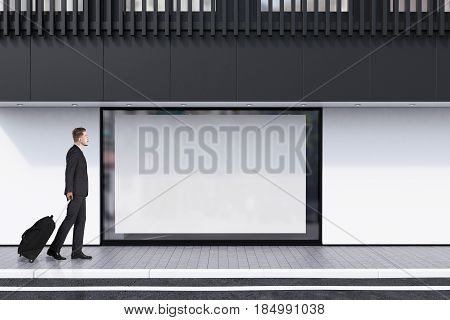 Man with suitcase passing by a shop window with a large horizontal poster and a black balcony on the second floor. Concept of promotion. 3d rendering mock up