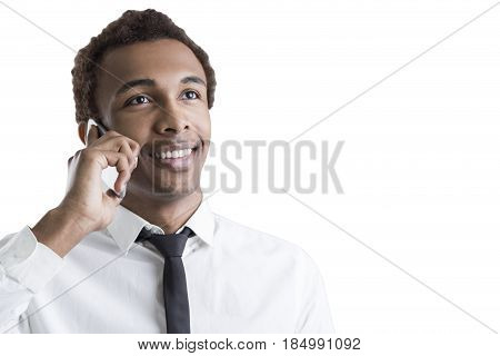 Isolated portrait of a young cheerful African American businessman with a smartphone looking upwards