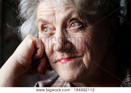 Elderly woman thoughtful face on a black background