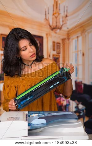 Beautiful woman wearing a brown blouse fixing a photocopier and smiling during maintenance.