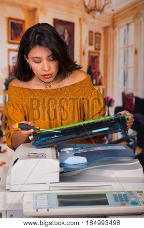 Beautiful woman wearing a brown blouse fixing a photocopier during maintenance using a screwdriver.