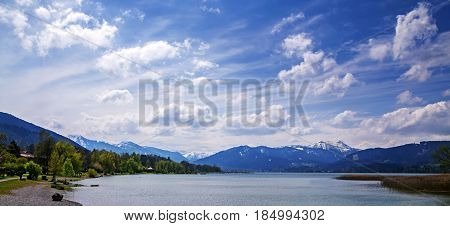 Panoramic view to lake tegernsee bavarian tourist resort with the alps in the background on a sunny spring day with cloudy blue sky bavaria germany europe copy space