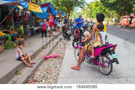 Bacong Philippines: 26 June 2016: Big family on pink motorbike by local market. Asian food market with local people from village. Philippines poor children. Simple people everyday lifestyle routine