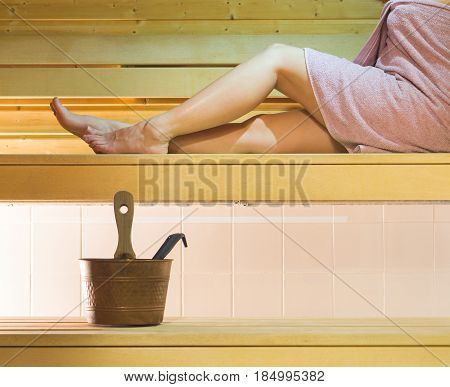 Young woman in Finnish city sauna. Girl enjoying the hot air and spending relaxed time. Traditional and authentic Finnish bathing and healthy lifestyle.