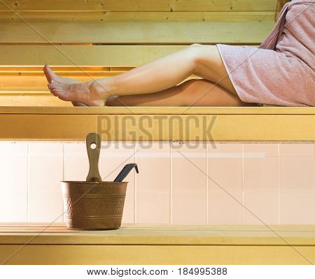 Woman laying on sauna bench wearing pink towel. Long legs resting and relaxing. Water bucket and ladle on wooden platform.
