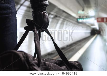 Terrorist in subway tunnel. Man planning bomb attack and strike in underground. Criminal standing in metro tunnel. Black bag and leather gloves. Security threat in public transportation concept.