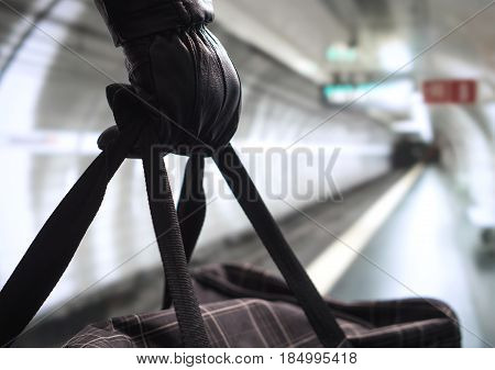 Close up of terrorist holding black bag in hand, possibly timebomb. Man planning a dangerous explosion in subway. Underground metro tunnel in the blurred background. Terrorism and security concept.
