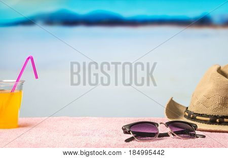 Summer holiday background with free empty blank copy space. Brimmed hat, sunglasses and yellow drink on towel in paradise lagoon beach with blue water and sky. Promotion template for spring discount.