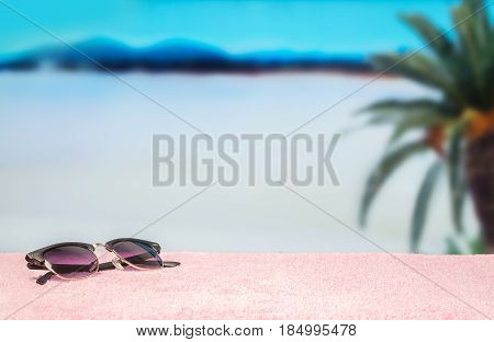 Beach background with free empty blank copy space. Trendy sunglasses on towel in beautiful paradise. Perfect lagoon beach and a palm tree in the blurred back. Clear sky and hot summer atmosphere.