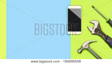 Smartphone fix background banner with a lot of free blank copy space for text and content for mobile phone repair company. Cellphone and tools on fun and colorful vibrant light green and blue table.