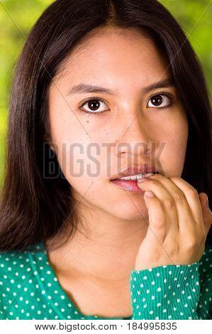 closeup of an anxious girl bitting nails.