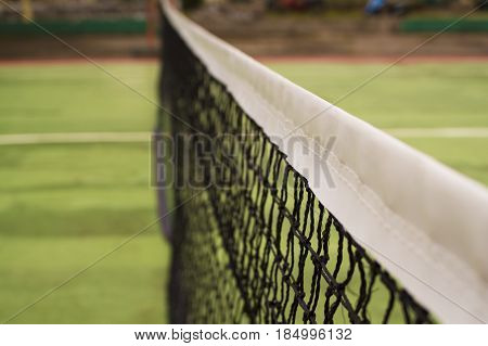 Tennis court net in warm sunlight. Tennis court divider. Opposite sites of competitors on tennis court. Summer day in tennis club. Outdoor sport and active lifestyle concept. Green field for game